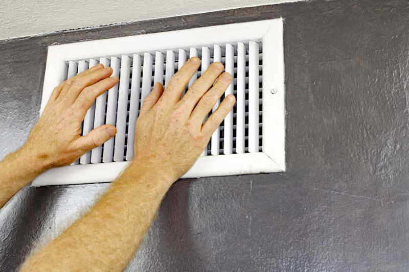 Two Hands in Front of an Air Vent